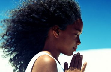 Image of a Black Girl with Natural Hair On The Beach Meditating and Practicing Self-Care in a white tank top.