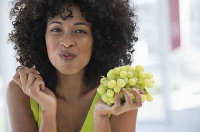 Black-woman-with-Natural-Hair-eating-grapes-and-smiling